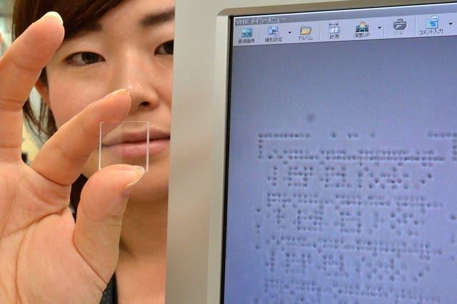Una investigadora de Hitachi muestra el prototipo y el monitor que permite ver las marcas microscópicas que contiene