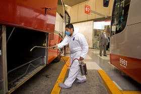 Un empleado desinfecta un ómnibus en la terminal de la ciudad de México