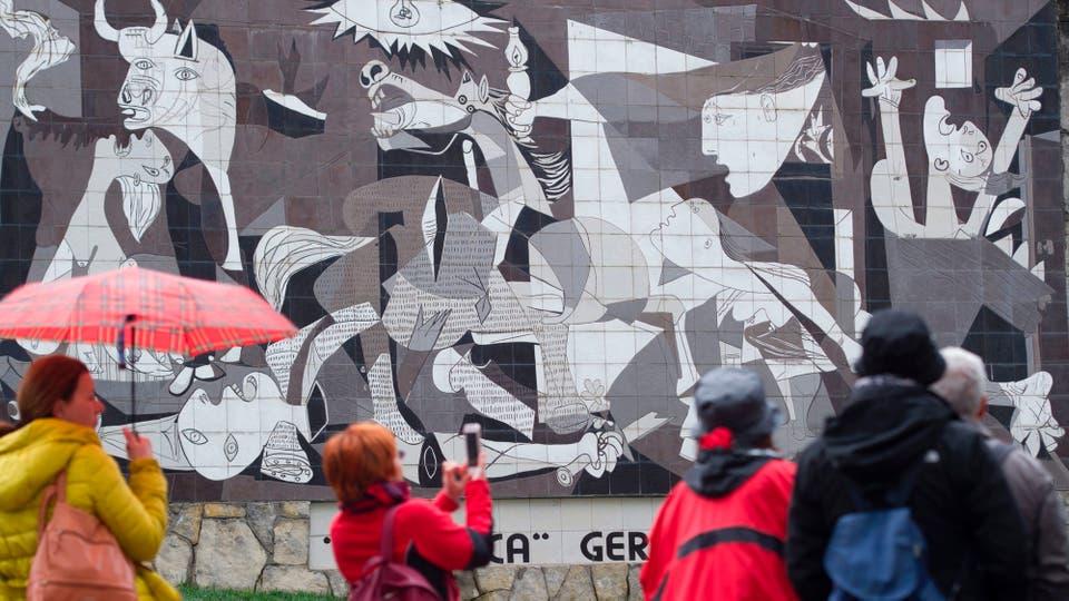 Varios turistas toman fotografías del mural . Foto: AFP / Ander Gillenea