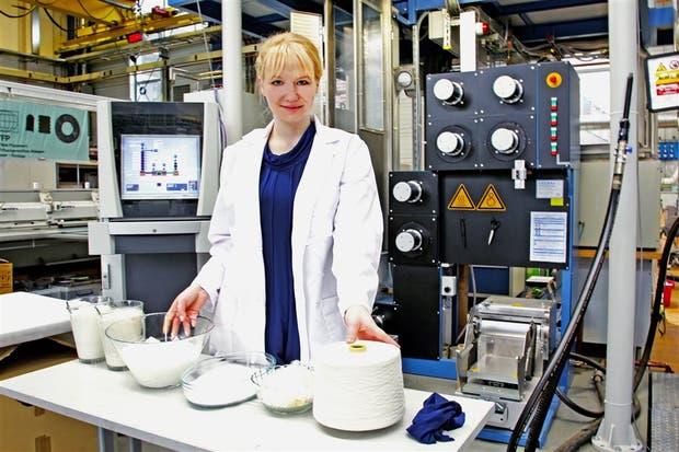 La microbióloga Anke Domaske en su laboratorio, con telas y fibras confeccionadas con leche desechada