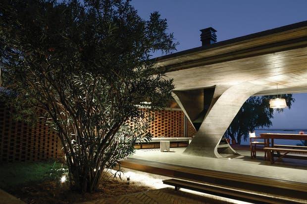 Esta ampliación, destinada a los usos sociales, se construyó en hormigón armado con un techo plano reforzado por cuatro vigas invertidas cuya carga converge en la columna que contiene el hogar..  /Mike Mercau