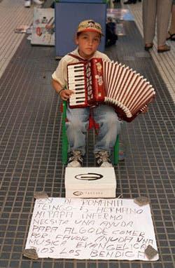 Un niño rumano toca el acordeón en la calle Florida