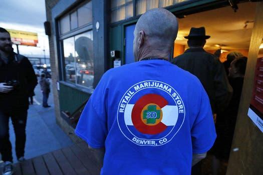 Los locales llegaron preparados con carteles y remeras a su primer día de venta de marihuana. Foto: AP