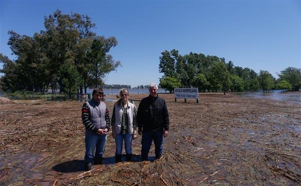 Los directivos de la Escuela Agropecuaria Nelly B. de Emerson, César Julián, Marina Justo y Néstor Montaya, delante de la entrada del colegio