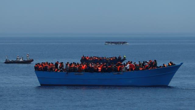 Los inmigrantes en una embarcacion de madera, aguardan ser rescatados por el buque de la ONG Malta-based Migrant Offshore Aid Station (MOAS) en el centro del Mediterráneo en aguas internacionales frente a la costa de Sabratha en Libia