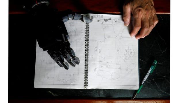 El ingeniero Chang Hsien-Liang, de 46 años, quien construyó su propio brazo utilizando la tecnología de impresión 3D, examina sus notas que muestran la condición de Angel Peng, de ocho años, que perdió la mano en Tainan,Taiwan