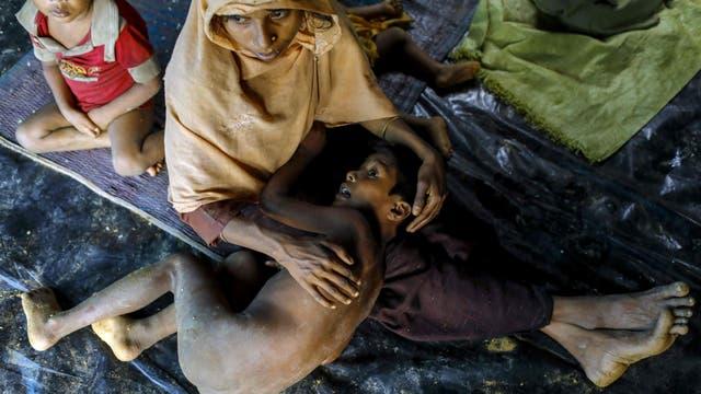 Un refugiado Rohingya de Myanmar sostiene a un niño mientras se sienta en un refugio improvisado cerca de la ciudad de Teknaf, Bangladesh