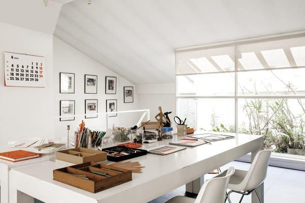En el área de trabajo en equipo, sillas tipo Eames ($380, Calma Chicha) y mesas blancas en madera y laminado hechas para una película..