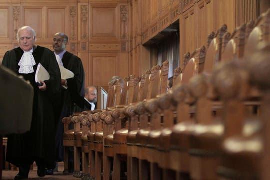 Jueces Christopher Greenwood, de Gran Bretaña, izquierda, y Abdulqawi Ahmed Yusuf de Somalia, segundo por la izquierda, entran en la Corte Mundial en La Haya. Foto: AP