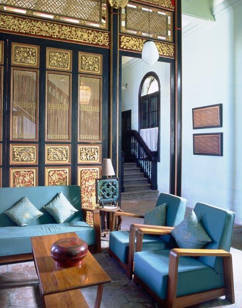 Las paredes doradas, con diseños chinos, crean un equilibrio perfecto con el living de líneas racionales..