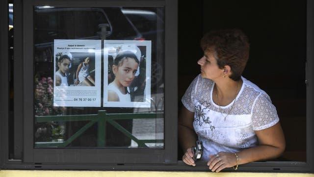 Una mujer mira un póster de Maëlys puesto por Gendarmería