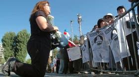 Una seguidora de Pinochet reza de rodillas frente a la Escuela Militar de Santiago