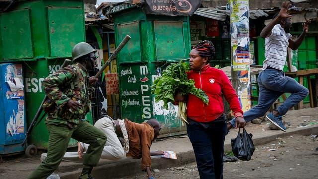Un policía anti-disturbios intenta dispersar a la gente de la calle cuando mientras una mujer lleva verduras en Mathare, Nairobi