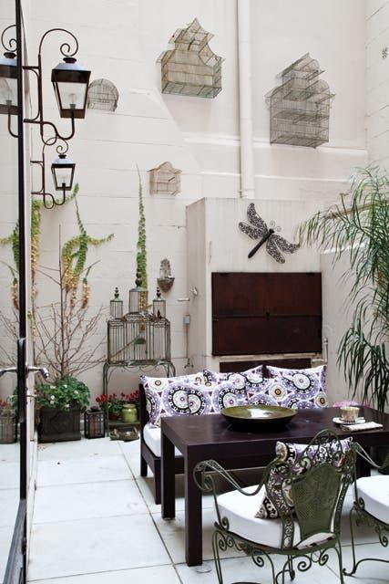 En el patio: sofá y mesa de 1,50x0,80m en hierro oxidado de (ambos de Arte Escondido) con almohadones tapizados por Inés. Faroles (Sentido).  Foto:Living /Magalí Saberián