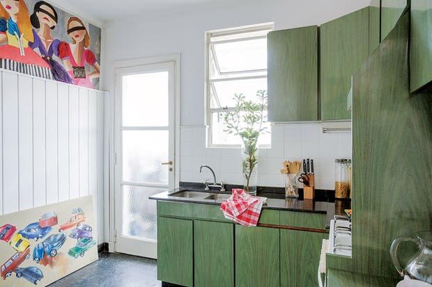 En la cocina, piso y mesada de granito negro y muebles en verde seco. En la pared opuesta, sobre el revestimiento de machimbre, obra de Carlota y afiches antiguos.  Foto:Living /Daniel Karp