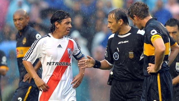 Héctor Baldassi habla con los jugadores Marcelo Gallardo y Martin Palermo después de nueve minutos de juego sobre su decisión de suspender el partido debido a la fuerte lluvia en el estadio La Bombonera en Buenos Aires el 21 de marzo. 2010. Foto: Archivo