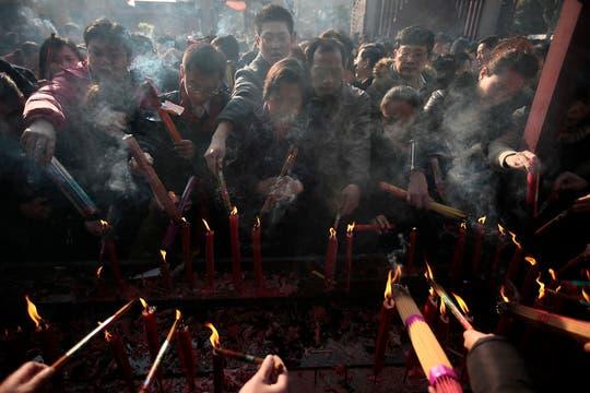 Los fieles encienden sus varitas de incienso para ofrecer la primera oración del nuevo año lunar en un templo en Shangai, China. Foto: AP