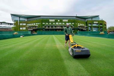 Un miembro del personal de jardinería de Wimbledon trabajando para mantener los estándares de las canchas, pese a no haber acción.