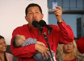 Con uno de sus nietos en brazos, Chávez muestra un ejemplar de la Constitución durante una conferencia de prensa