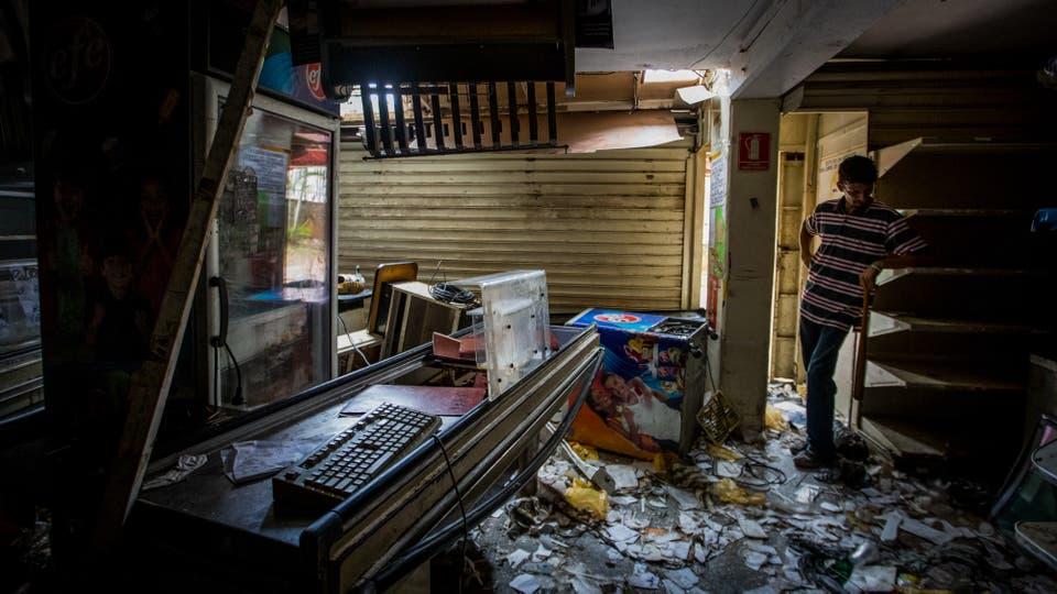 Un hombre observa los destrozos ocasionados en una tienda que fue saqueada anoche en Caracas. Foto: EFE / Miguel Gutierrez