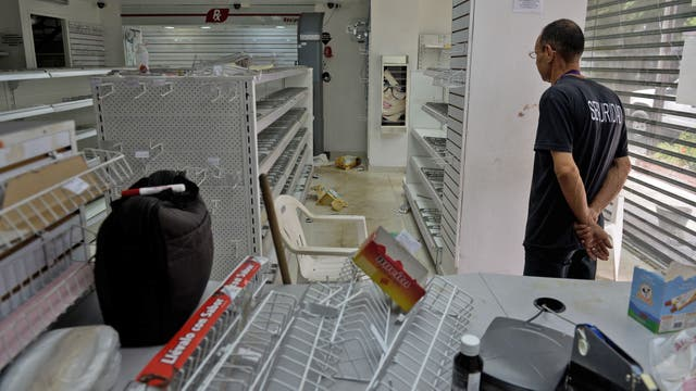 Un guardia de seguridad vigila una farmacia que fue vaciada por la profunda crisis que atraviesa Venezuela.