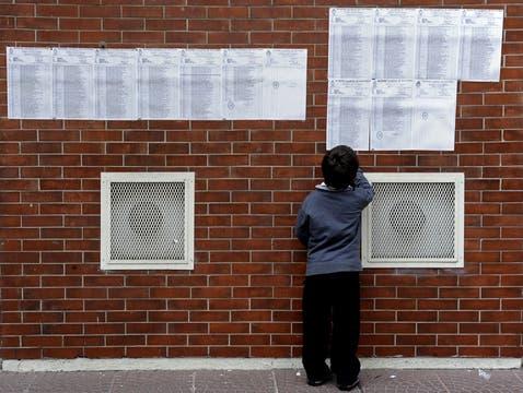 Un niño busca el nombre de su padre en el padrón electoral. Foto: AFP