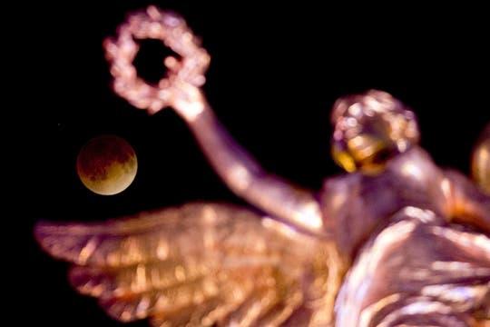 La luna pasa sobre el Monumento a la Independencia en la ciudad de México. Foto: AFP