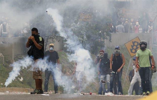 Un grupo de manifestantes se planta con máscaras contra los gases lacrimógenos, ayer, en Caracas
