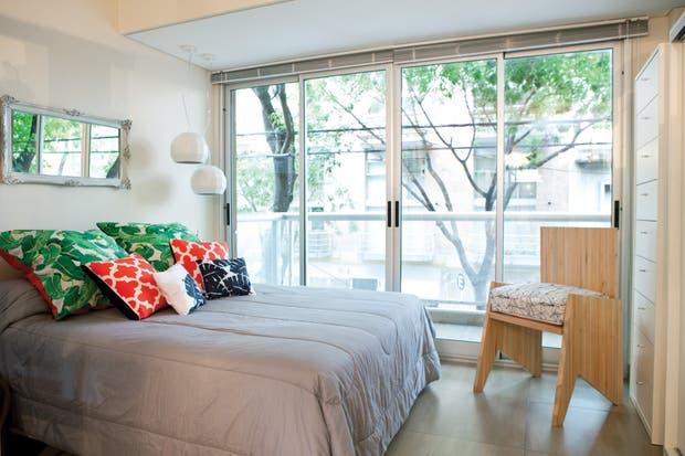La cama, ubicada en el centro de la habitación, tiene un espejo heredado de sus abuelos en la cabecera que ayuda a ampliar visualmente el espacio. Dos lámparas facetadas, que caen ligeramente al costado de la cama son la única iluminación.  /Javier Picerno