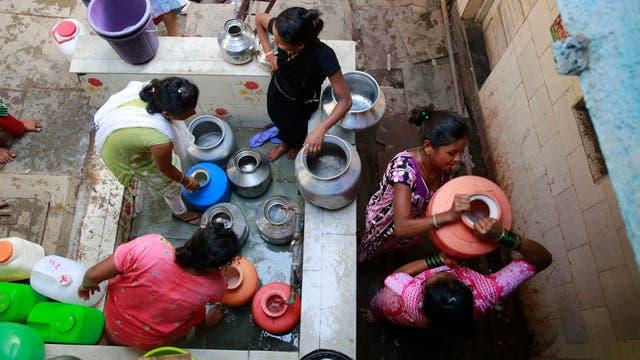 Un grupo de mujeres junta agua en jarras en Mumbai, India
