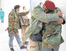 Dos rebeldes lloran la muerte de un compañero de armas en un hospital de Ajdabiya