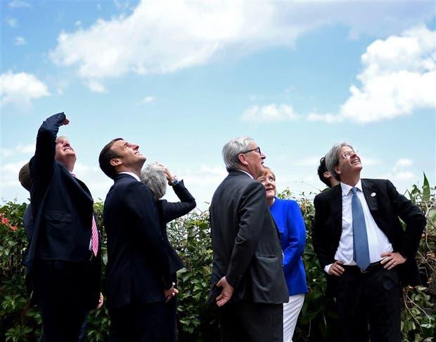 En un alto de la cumbre, Trump, Macron, May, Juncker, Merkel y Gentiloni miran los aviones militares italianos