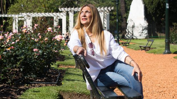 Sandra, sentada en el banco que llevará la placa de su esposo