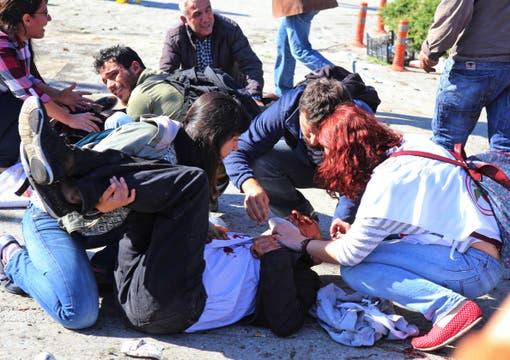 Manifestantes atienden a uno de los heridos tras las dos explosiones en Ankara