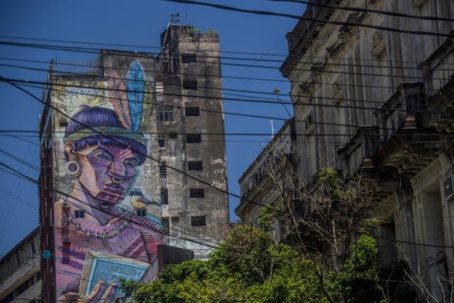 Grafiti en Asunción de un indígena que lee un libro en inglés