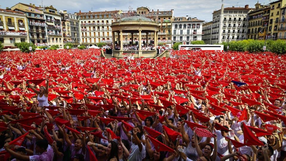 Miles de personas festejan en la Plaza del Castillo de Pamplona, con sus pañuelos rojos alzados, el inicio de las fiestas de San Fermín. Foto: EFE / Daniel Fernandez