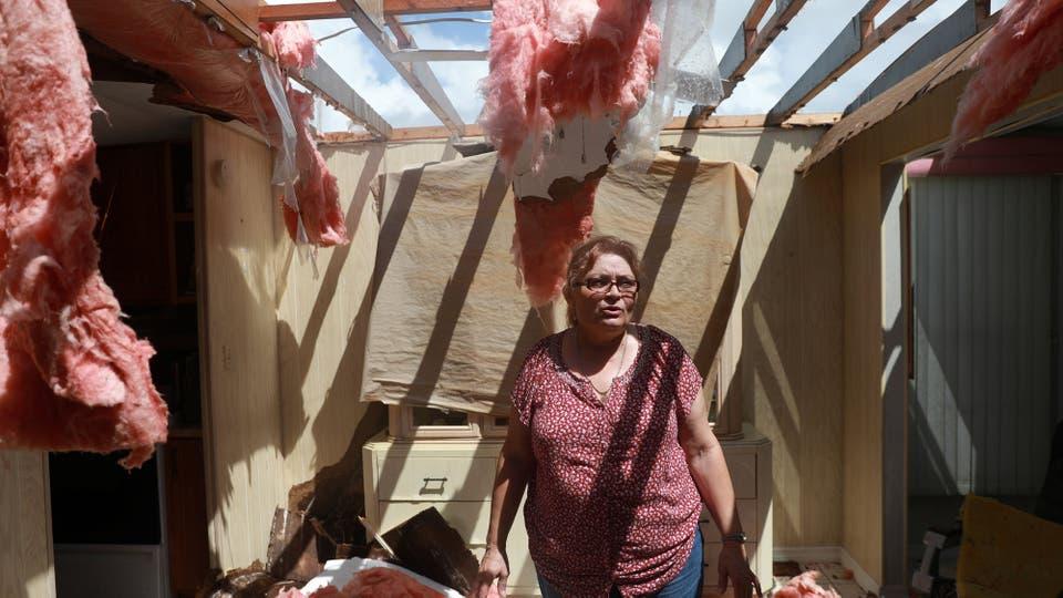 Una mujer intenta rescatar algunas de sus pertenencias . Foto: Reuters