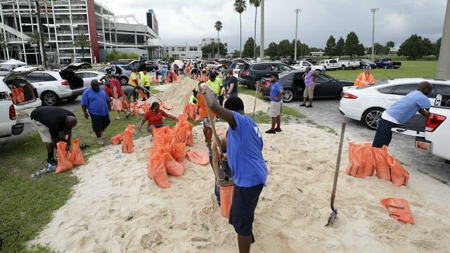 Empleados públicos de Orlando y ciudadanos preparan bolsas con arena como parte de los preparativos para recibir al huracán Irma
