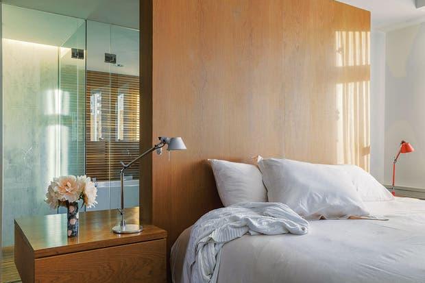 La división virtual entre el cuarto y el baño está inspirada en el hotel Fasano de Río de Janeiro: en este caso, se realizó en madera.  Foto:Living /Daniel Karp