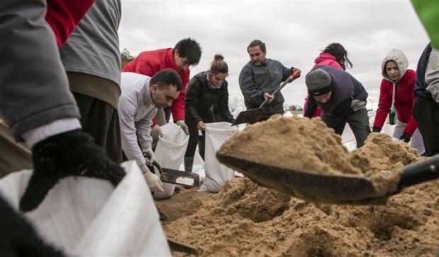 Los vecinos llenan bolsas con arena para usarlas como barreras