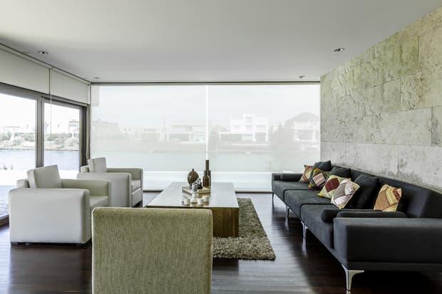 Para contener el mobiliario moderno de este living se optó por cubrir una pared con un revestimiento símil piedra.  /Archivo LIVING