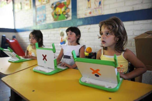 Niños junto a computadoras educativas OLPC