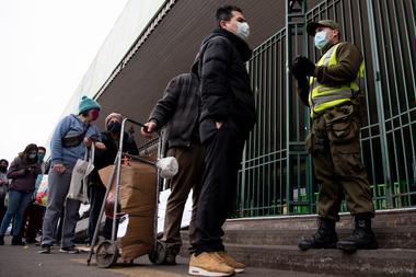 La gente hace cola en un mercado popular en Santiago, el 22 de junio de 2020, en medio de la pandemia de coronavirus