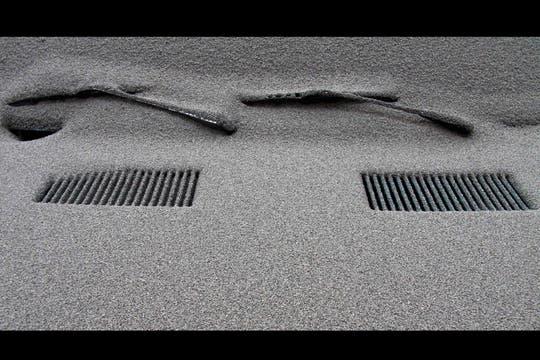 La parte delantera de un auto apenas se distingue bajo la densa capa de ceniza. Foto: AP