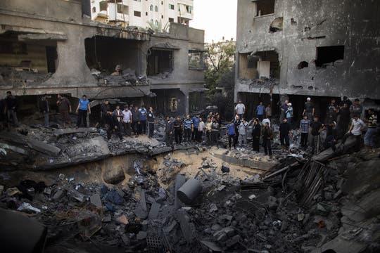 Palestinos se reúnen alrededor de un cráter causado por un ataque aéreo israelí en casa de la familia al-Dallu en la ciudad de Gaza. Foto: AFP
