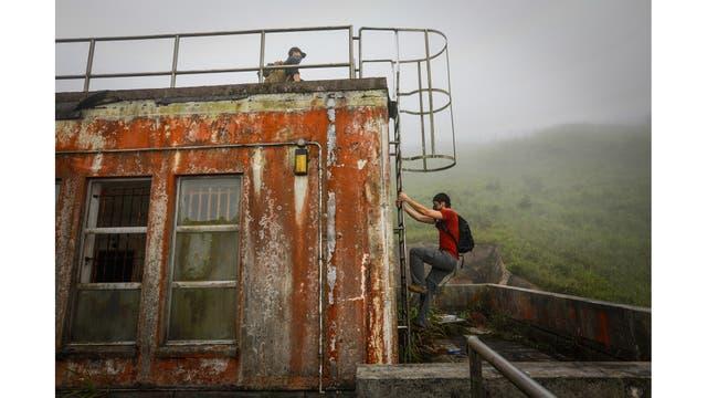 Un miembro de HK URBEX sube una escalera en un cuartel abandonado del ejército británico en Hong Kong