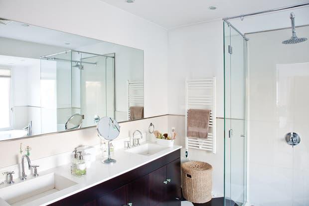 El baño en suite tiene box de ducha y jacuzzi con grifería del diseñador francés Philippe Starck y revestimiento de pared en porcelanato (todo de Barugel Azulay)..