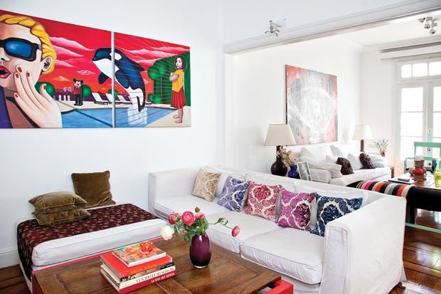 Sofá blanco con almohadones con motivos de arabescos (Falabella) separa el sector social del área de TV y entretenimientos. En la pared, obra firmada por Solá..  Foto:Living /Javier Csecs