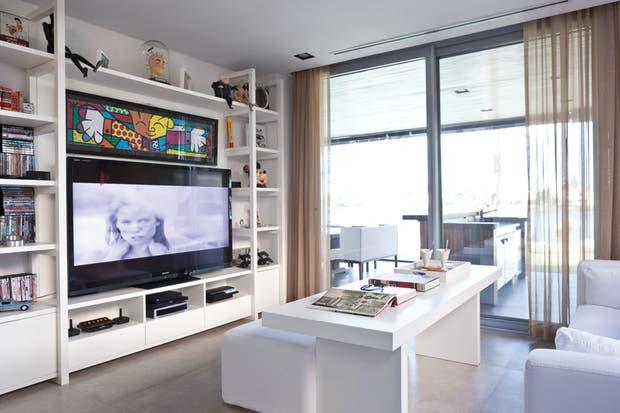 """En el mueble tipo biblioteca de cedro en color blanco ($45.000, Modo Casa) se colocó un LED de 50"""" ($14.580, Sharp) y consolas de juegos. """"El living es una opción más que complementa la isla, donde también es posible juntarse y cenar"""".  /Javier Picerno"""