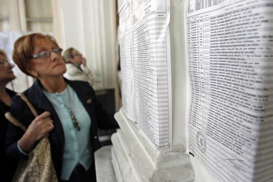 En un escuela de la Capital una mujer busca el los padrones su nombre para poder votar. Foto: EFE
